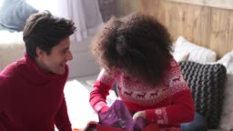 Woman opening christmas gift and embracing her boyfriend