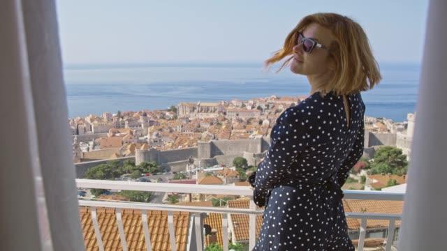 MS Woman opening curtains and door to balcony overlooking Dubrovnik,Croatia