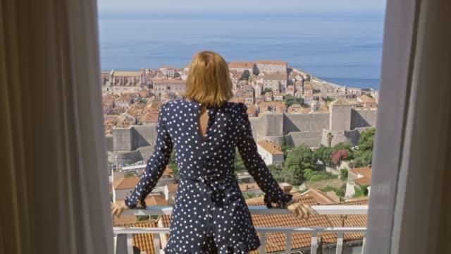 vidéos et rushes de woman ms ouvrir les rideaux et monter sur le balcon ensoleillé surplombant dubrovnik, croatie - croatie