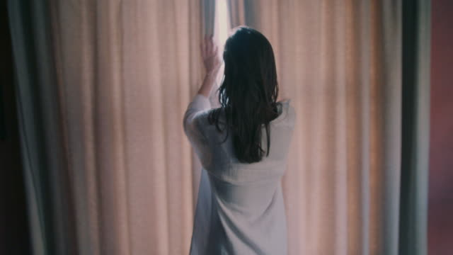 woman opening curtains in morning - tenda video stock e b–roll