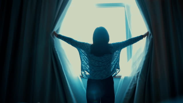 woman opening curtains in the room - open stock videos & royalty-free footage