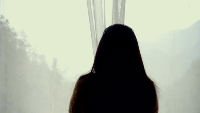 woman opening curtains of room