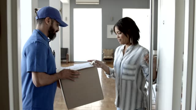 woman opening door and receiving package from delivery man - delivering stock videos & royalty-free footage