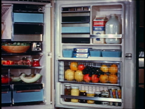 stockvideo's en b-roll-footage met 1958 woman opening door of refrigerator filled with food - vol fysieke beschrijving