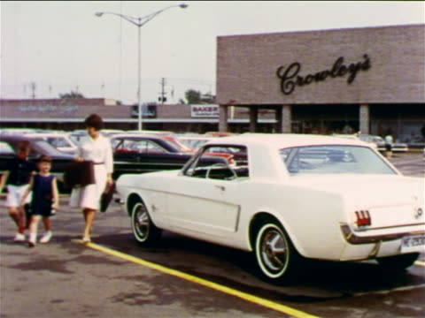 1965 woman opening door of white Ford Mustang for two children in shopping mall parking lot