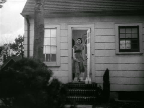 B/W 1939 woman opening door to house + taking milk bottles from step / Morning / educational