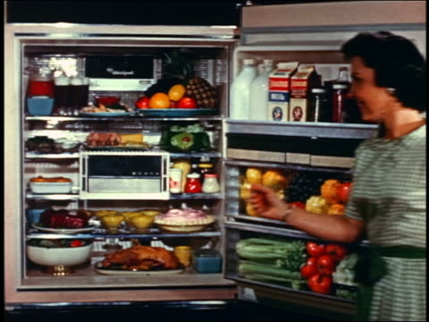 1958 pan woman opening doors of massive refrigerator / freezer packed with food - full stock videos & royalty-free footage