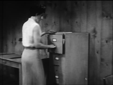 b/w 1957 woman opening file cabinet + looking through files in office - filing cabinet stock videos and b-roll footage