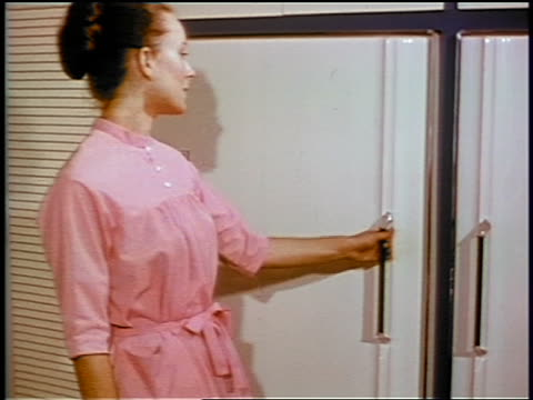 1969 woman opening freezer + reaching for Stouffer's frozen food / industrial