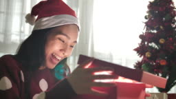 Woman opening gift box in Christmas at home