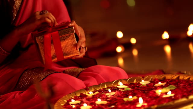 CU Woman opening gift during diwali festival