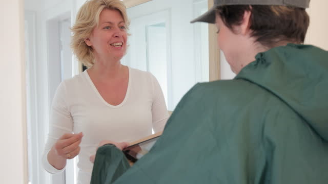 woman opening her front door and receiving a package - door stock videos & royalty-free footage