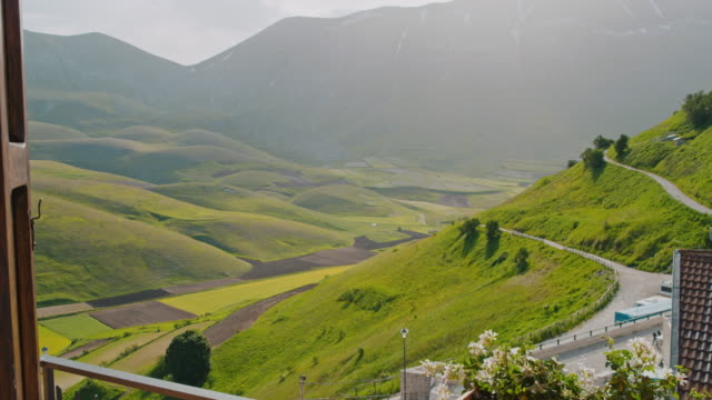 ms woman opening hotel curtains to reveal sunny mountain view, castelluccio, umbria, italy - curtain stock videos & royalty-free footage