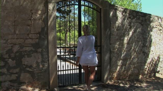 vidéos et rushes de femme ouverture porte en fer - portail