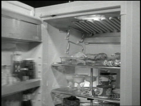 b/w 1959 woman opening large refrigerator + removing food - 1959 stock videos & royalty-free footage