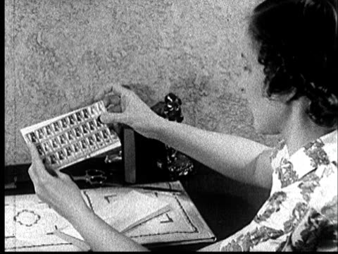 1935 cu woman opening letter and finding a sheet of stamps/ audio - briefmarke stock-videos und b-roll-filmmaterial