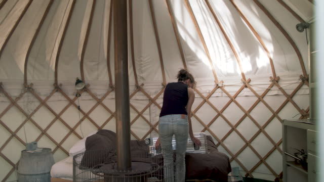 Woman opening luggage on bed in yurt