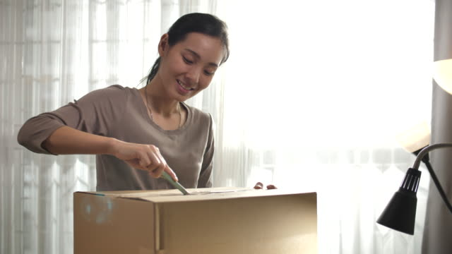 vídeos de stock, filmes e b-roll de mulher que abre a caixa de entrega em linha da compra em casa - pacote arranjo