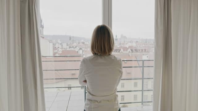 WS-Frau Öffnen der Vorhänge in ihrer Wohnung außerhalb aussehen