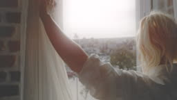 SLO MO Woman opening the curtains in her apartment