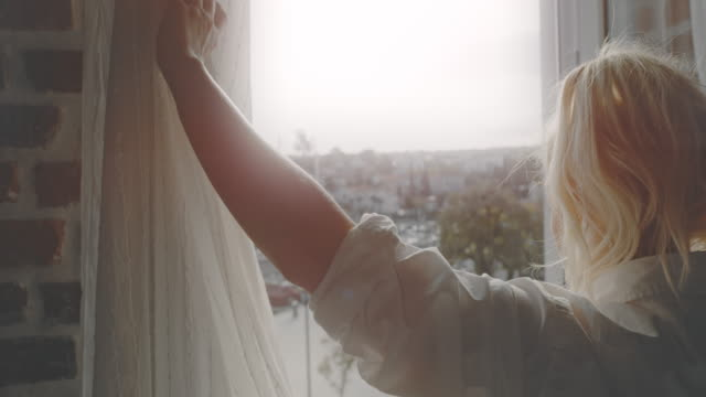 slo mo woman opening the curtains in her apartment - balcony stock videos & royalty-free footage