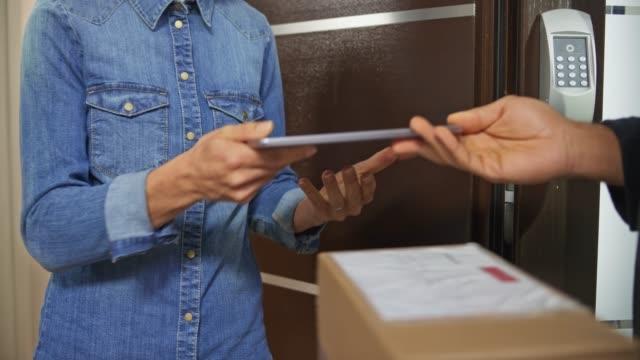 フロントドアを開けて、彼女に配達されているパッケージに署名する女性 - 小荷物点の映像素材/bロール