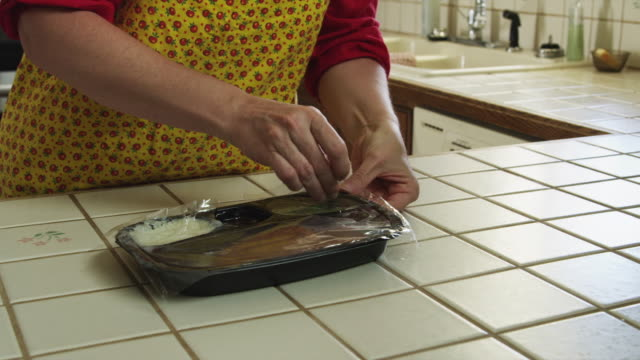 MS TU Woman opening TV dinner in kitchen / Provo, Utah, USA