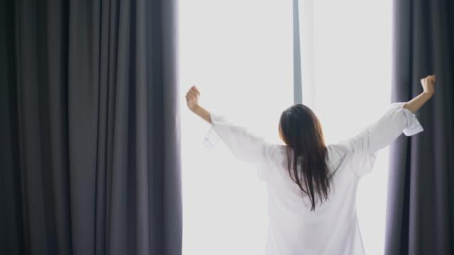 Frau Öffnung Fenstervorhänge nach dem Aufwachen morgens