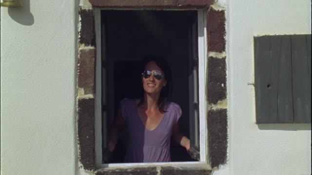 vídeos de stock e filmes b-roll de ms woman opening window shutters and looking up at sun / santorini, greece - janela aberta