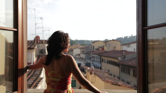 mh ds woman opening windows overlooking old town rooftops / florence, italy - window点の映像素材/bロール