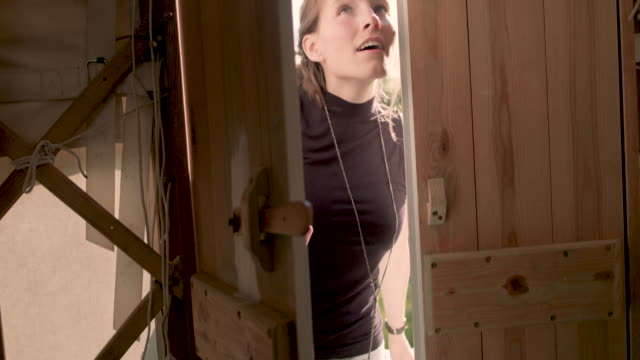Woman opening wooden door to yurt