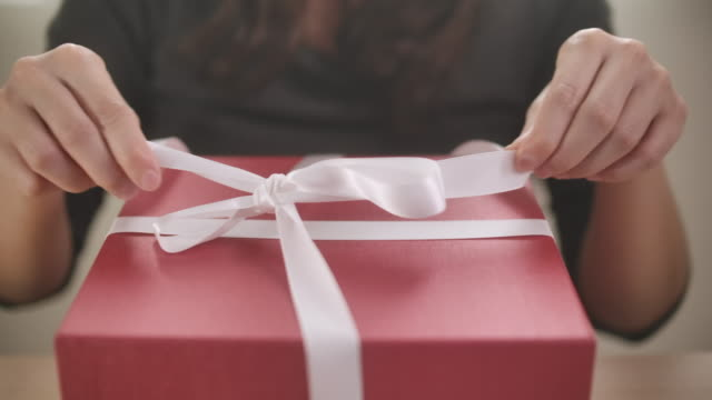 woman opens a gift box at home, unwrapping gift box - unwrapping stock videos & royalty-free footage