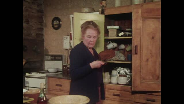 vidéos et rushes de woman opens a kitchen cupboard, 1970s - placard