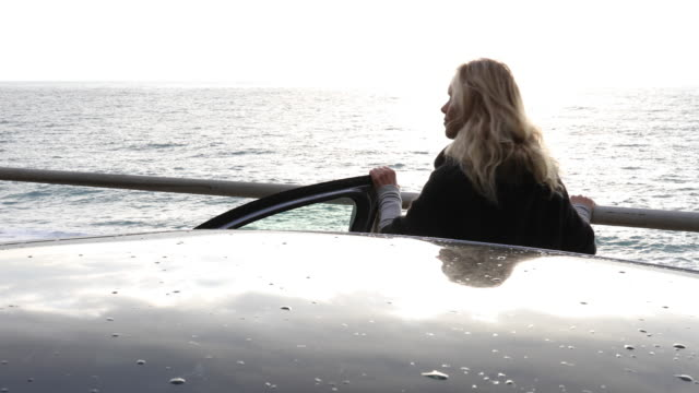 Woman opens car door, takes step to sea railing
