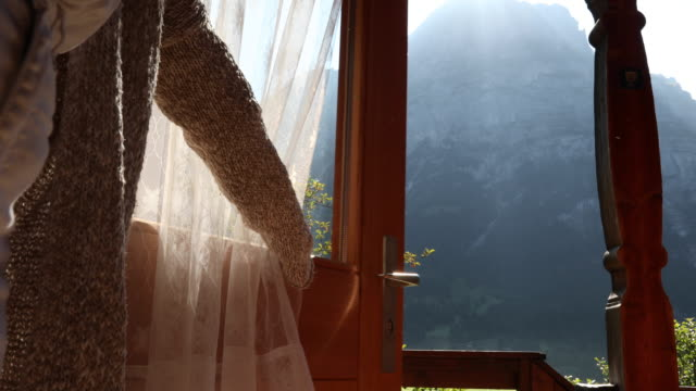 Woman opens chalet door, looks out to mountain view