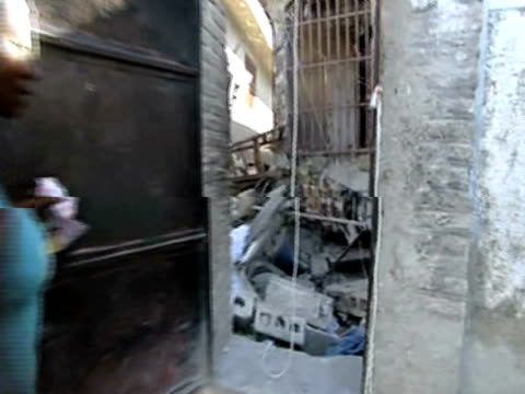 vídeos de stock e filmes b-roll de woman opens compound door to reveal destroyed house with bodies trapped underneath following devastating earthquake haiti 15 january 2010 - hispaniola