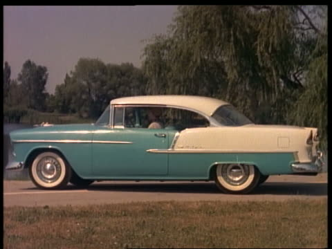 stockvideo's en b-roll-footage met 1955 woman opens door of blue + white chevrolet bel air + starts to get out in driveway - 1955