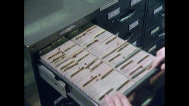 woman opens filing cabinet and looks through files - 以前の点の映像素材/bロール