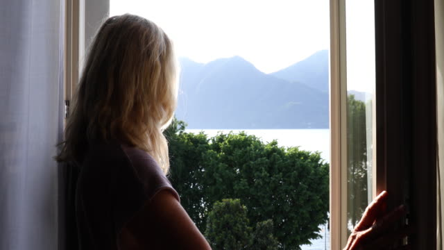 Woman opens french door, looks out over lake