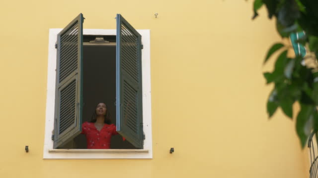 vídeos y material grabado en eventos de stock de a woman opens shutters on a window traveling in a luxury resort town in italy, europe. - slow motion - aspirations