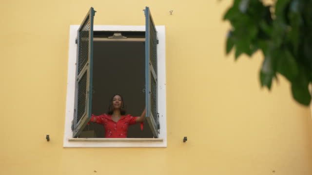 A woman opens shutters on a window traveling in a luxury resort town in Italy, Europe. - Slow Motion