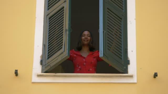 vídeos de stock, filmes e b-roll de a woman opens shutters on a window traveling in a luxury resort town in italy, europe. - slow motion - descoberta