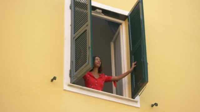 vídeos de stock e filmes b-roll de a woman opens shutters on a window traveling in a luxury resort town in italy, europe. - slow motion - janela aberta
