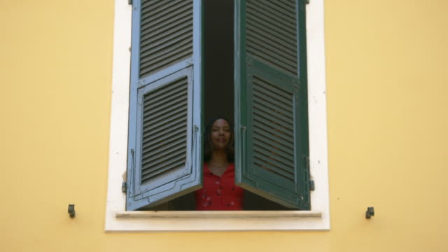 a woman opens shutters on a window traveling in a luxury resort town in italy, europe. - slow motion - shutter stock videos & royalty-free footage