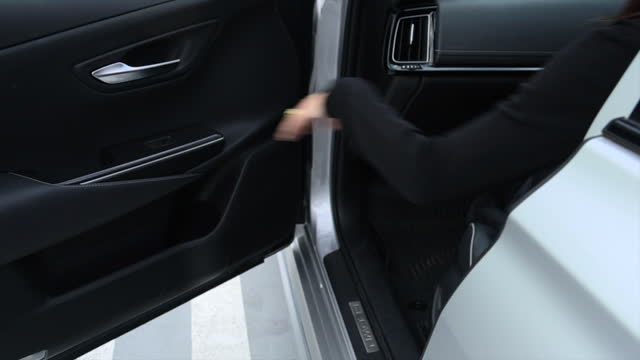 woman opens the car door and gets in the car at the parking. woman opening door of automobile. slow motion. - closing stock videos & royalty-free footage