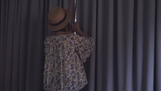 Woman opens the curtains and walking out.