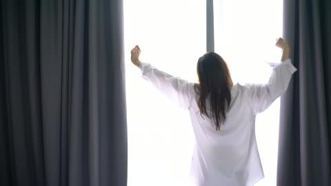 stockvideo's en b-roll-footage met vrouw opent de gordijnen in de ochtend - comfortabel