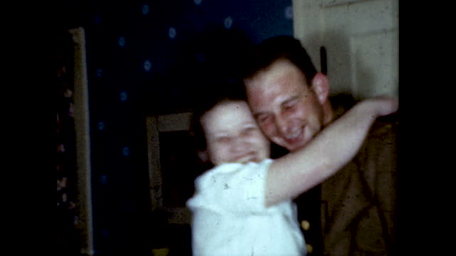 woman opens the door and it's her husband dressed in his army uniform returning home from war. - colour image stock videos & royalty-free footage