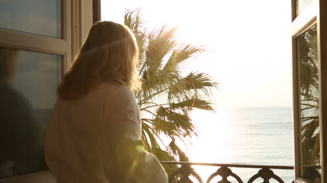 Woman opens veranda doors, looks out to sea