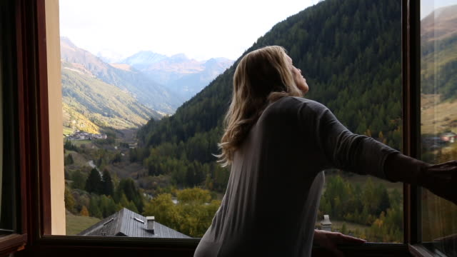 woman opens window shutters, look out to mountain scene - open window stock videos and b-roll footage